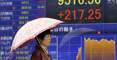 A kimono-clad woman walks past an electronic share price board displayed in the window of a securities firm in Tokyo on September 15, 2010. Japanese shares strongly rebounded on September 15 after the government intervened in the forex markets to sell down the yen to help uplift the all-important export sector. The Nikkei index gained 2.34 percent or 217.25 points to 9,516.56.   AFP PHOTO/Kazuhiro NOGI (Photo credit should read KAZUHIRO NOGI/AFP/Getty Images)